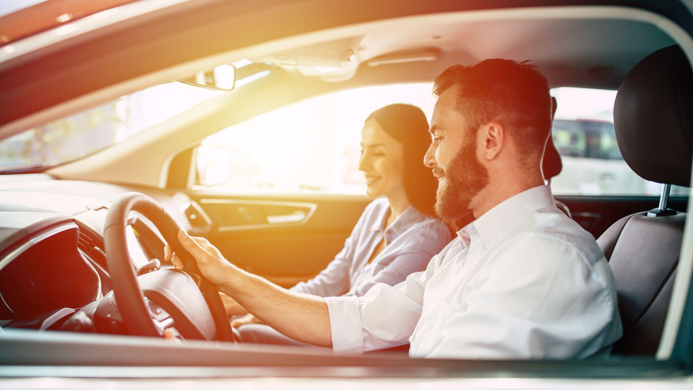 Junger Mann und junge Frau lächelnd im Auto bei einer Probefahrt