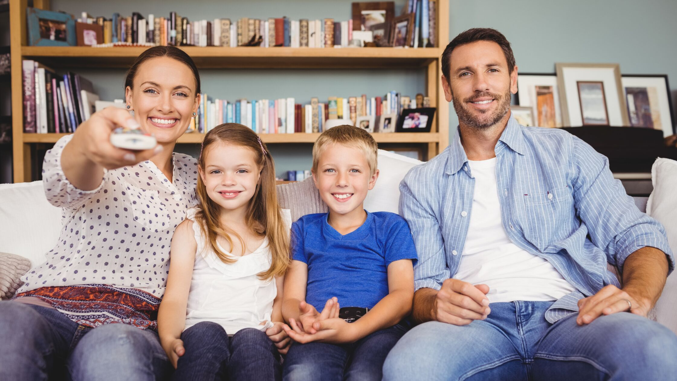 Rundfunkbeitrag nach Umzug: Eltern mit zwei Kindern sitzen auf dem Sofa und sehen fern