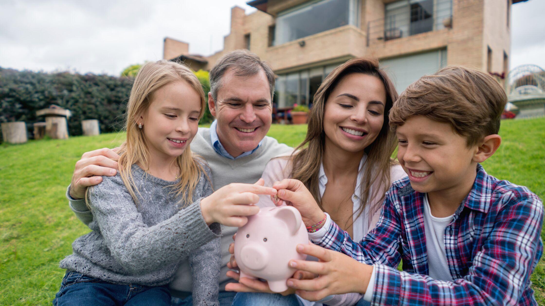 Eltern mit zwei Kindern sitzen vor ihrem Haus und werfen gemeinsam eine Münze in ein Sparschwein