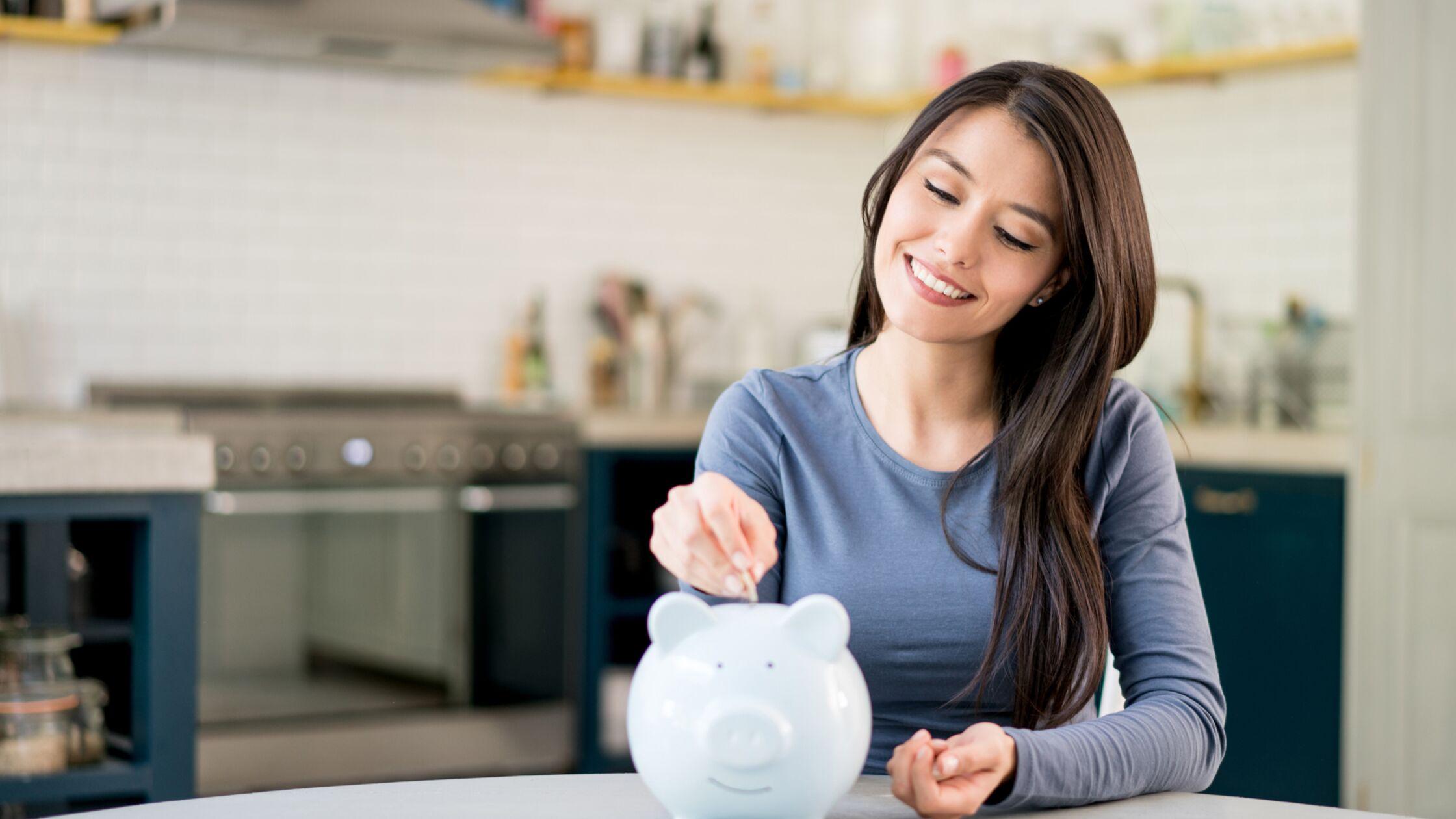Junge Frau spart Geld in einem Sparschwein