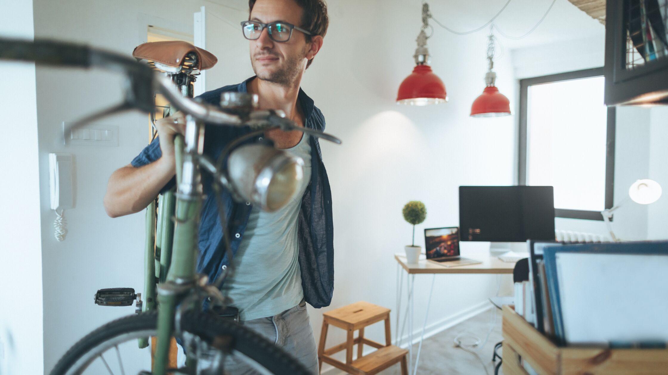 Mann trägt Fahrrad ins Wohnzimmer