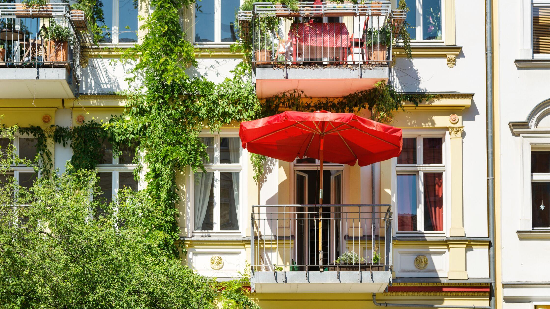 Außenansicht eines größeren Mietshauses mit bepflanzten Balkons und Sonnenschirm