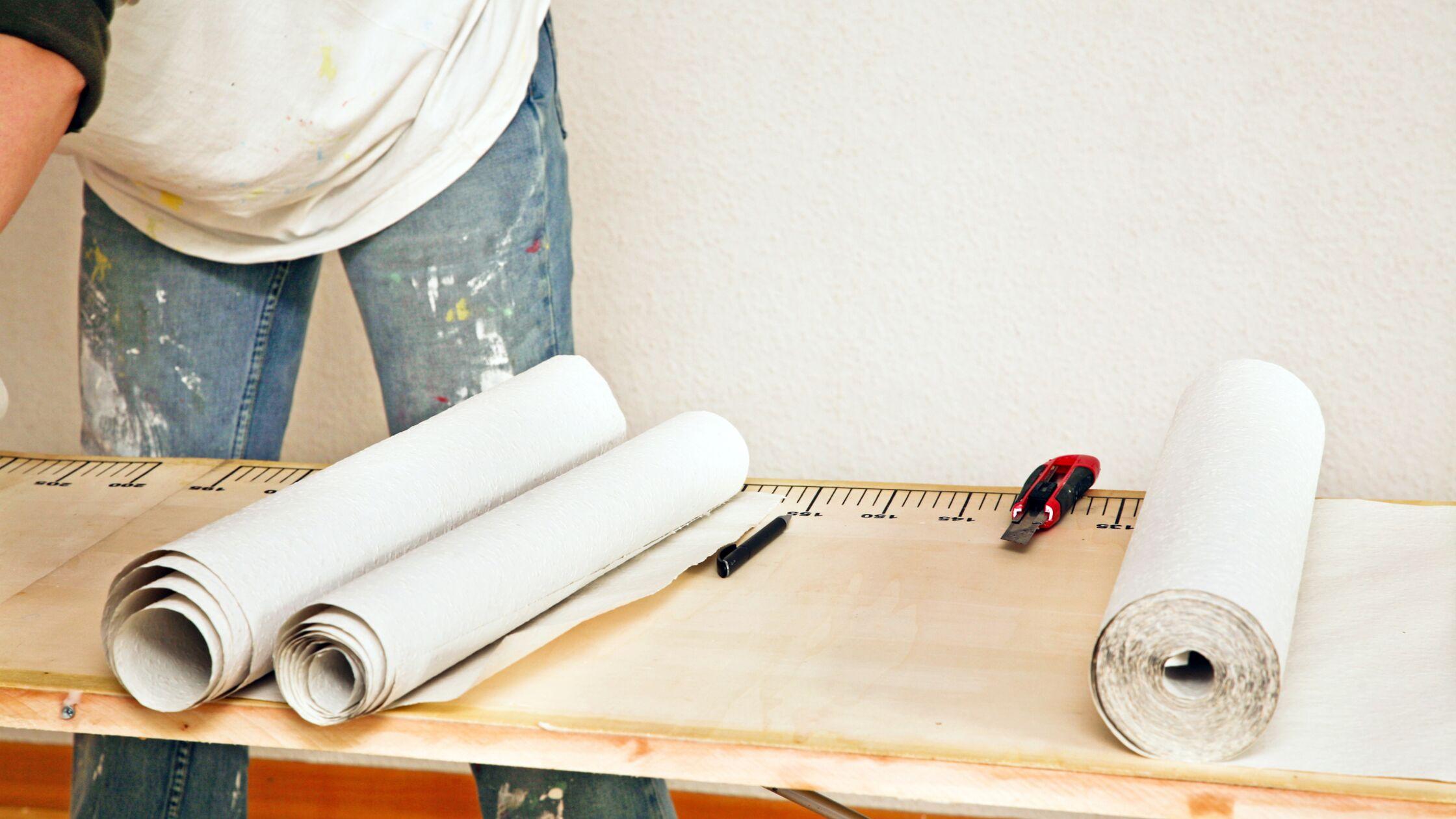 Frau steht mit farbverschmierten Jeans am Tapeziertisch und schneidet Tapeten zu