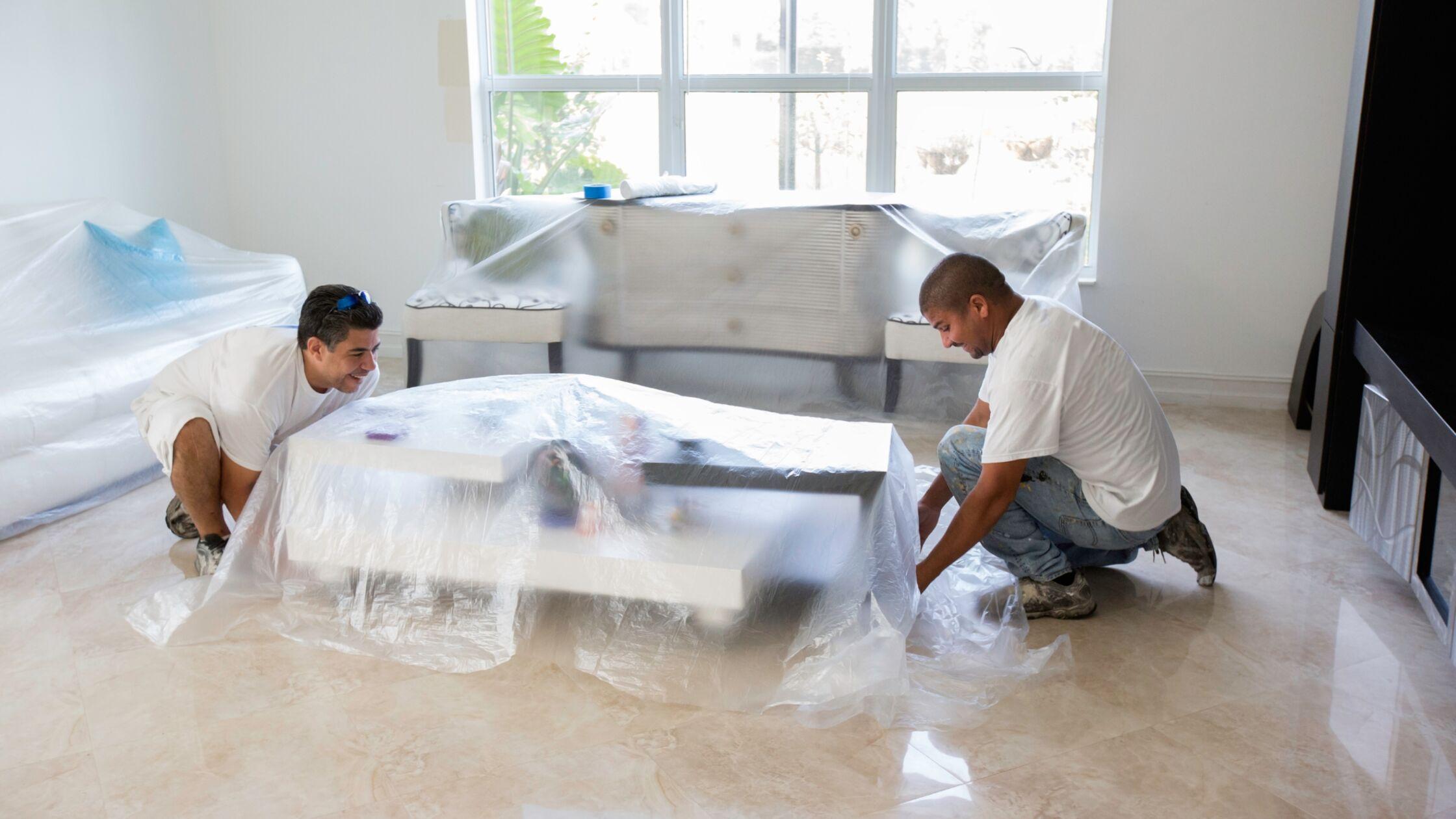 Männer decken Möbel mit Folie ab