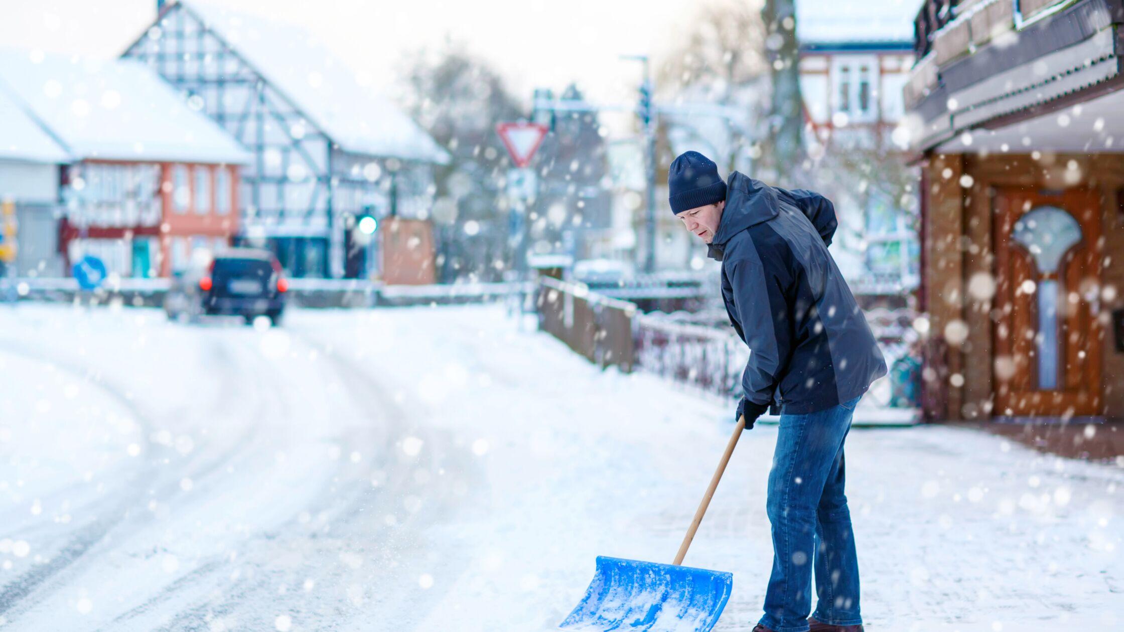 Mann räumt Schnee im Winter mit Schaufel
