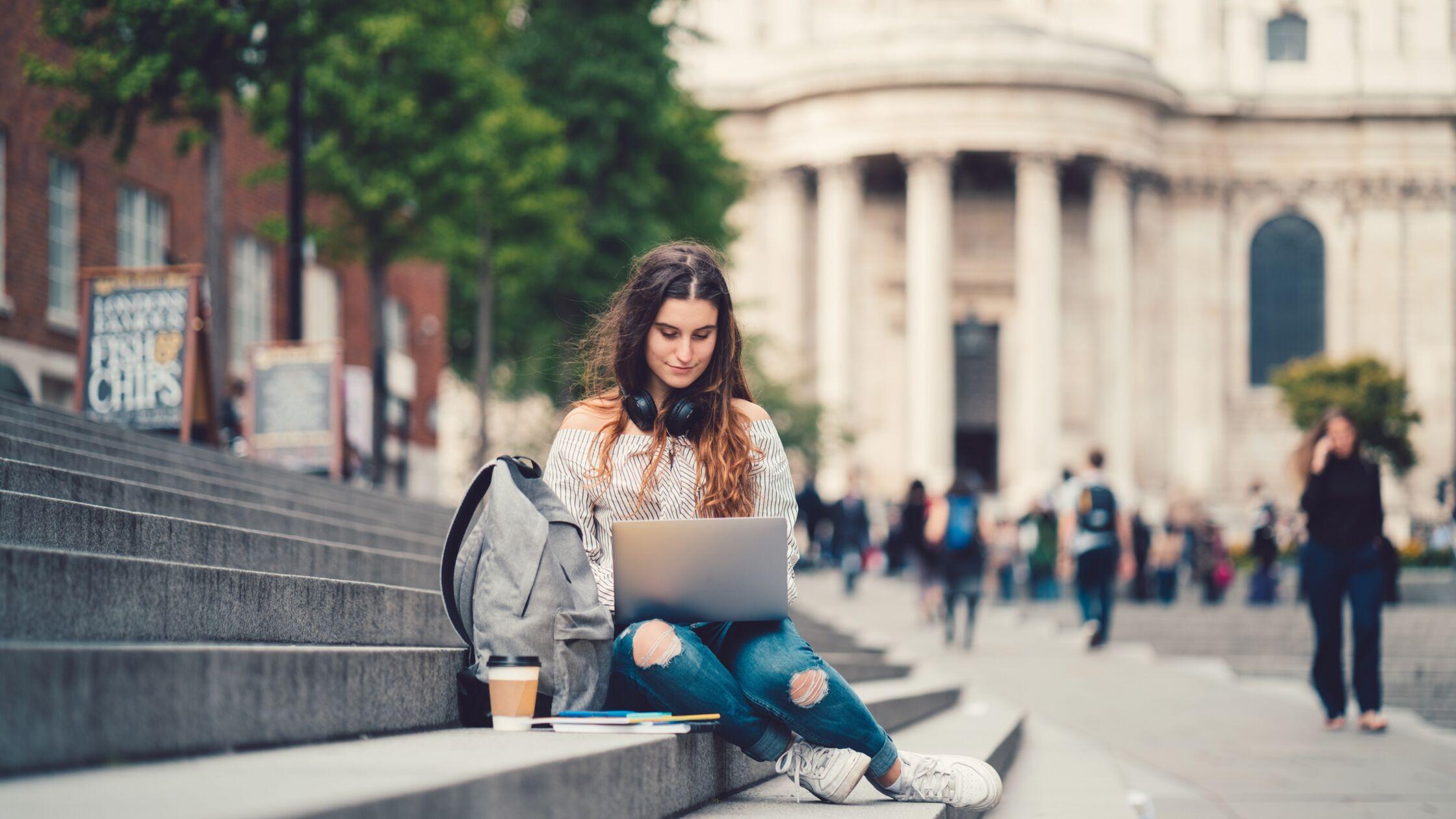 Studentin sitzt an Laptop und vermeldet Umzug