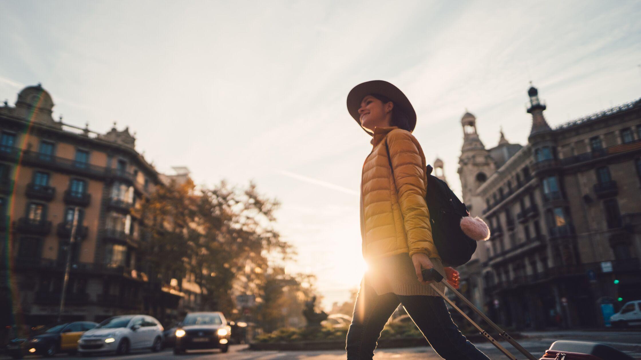 Frau zieht mit Koffer freudig ins Ausland