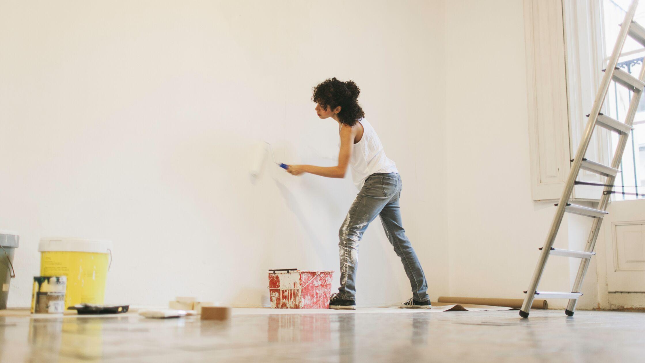 Junge Frau streicht Wände weiß