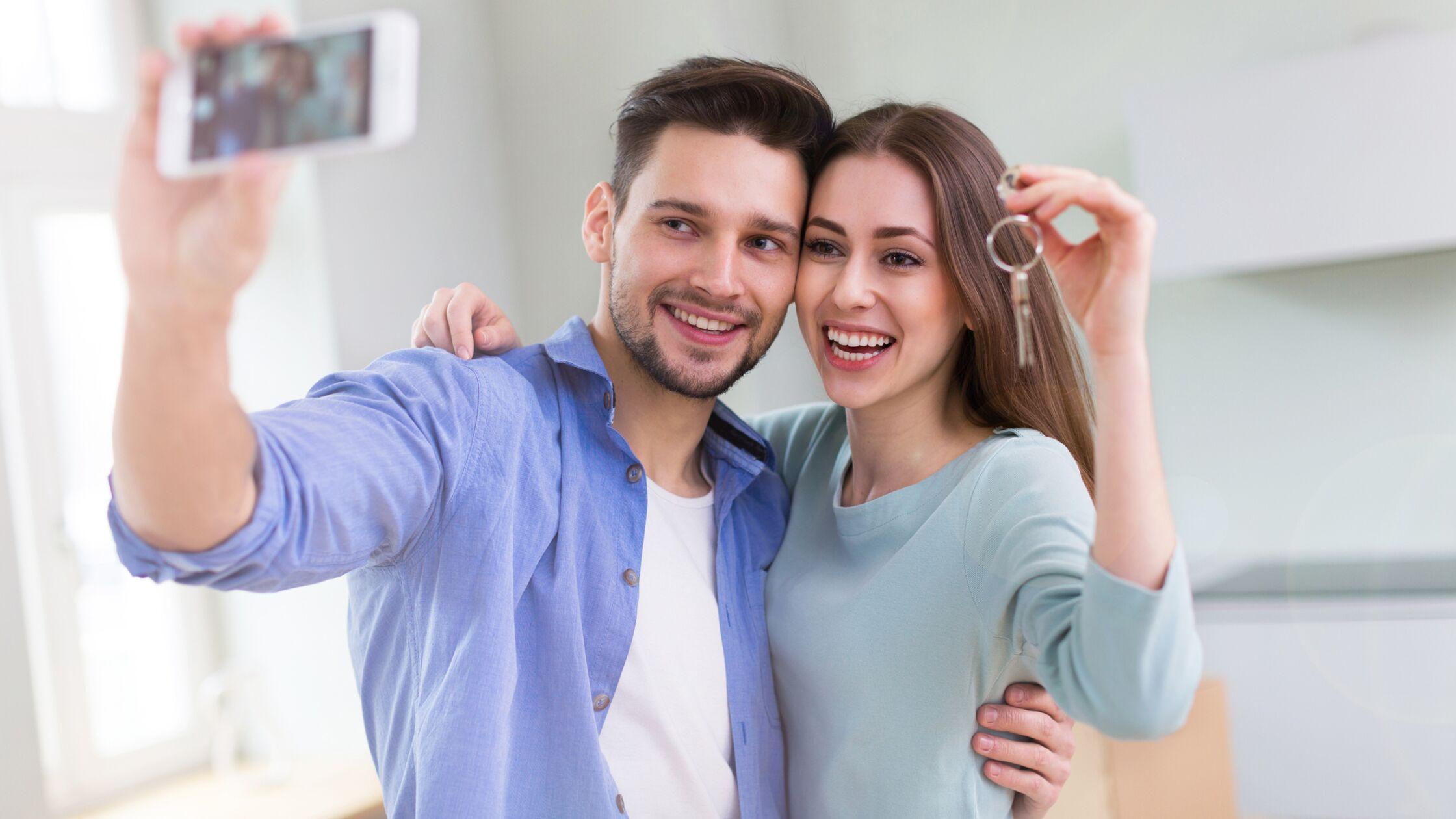 Junges Paar hält Schlüssel zu neuer Wohnung hoch und macht Selfie