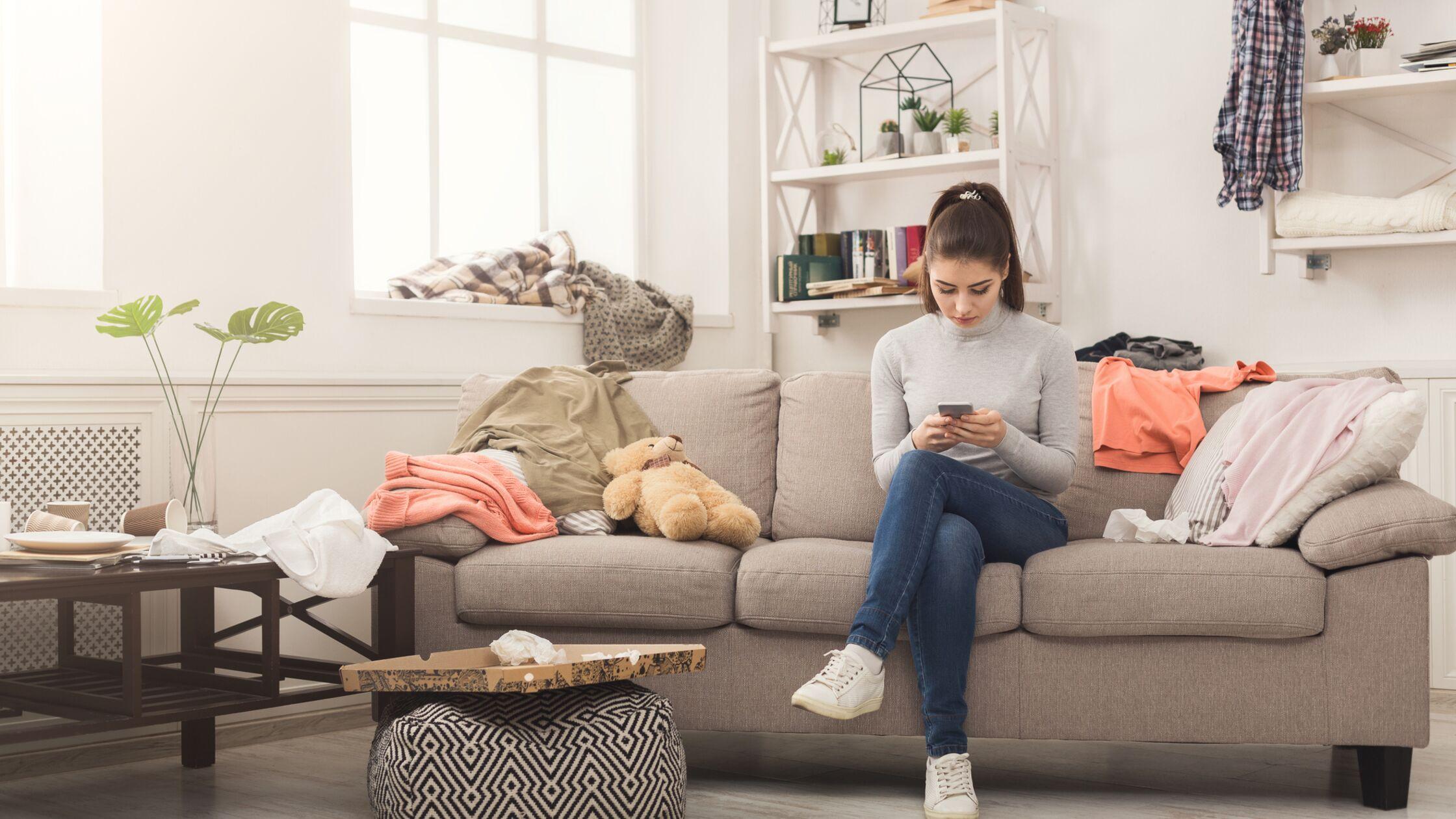 Junge Frau sitzt in chaotischem Wohnzimmer auf der Couch