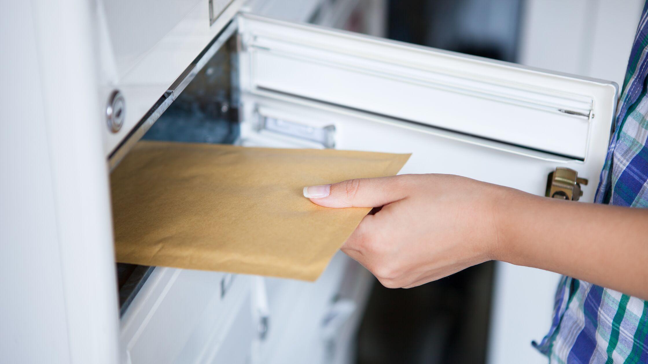 Frau nimmt einen Umschlag aus einem Briefkasten.
