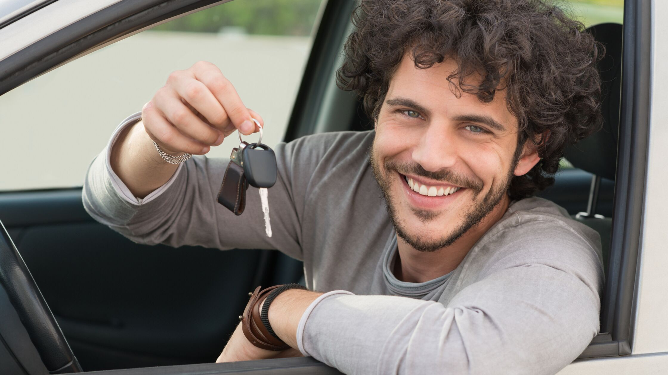 Mann sitzt hinter dem Lenkrad eines Autos und hält Autoschlüssel aus dem Fenster