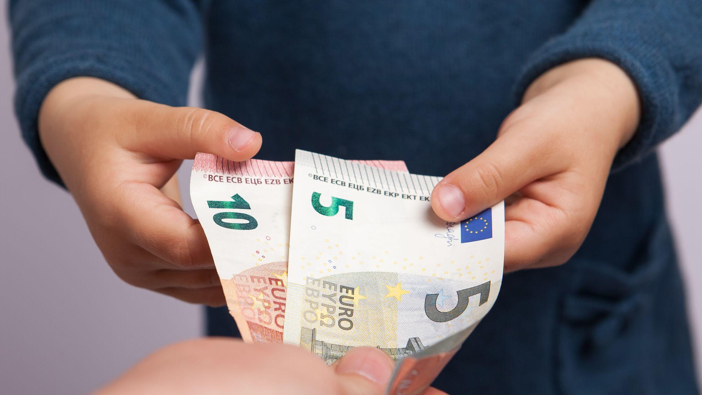 Kinderhände greifen nach Geldscheinen, die eine Hand hinhält.