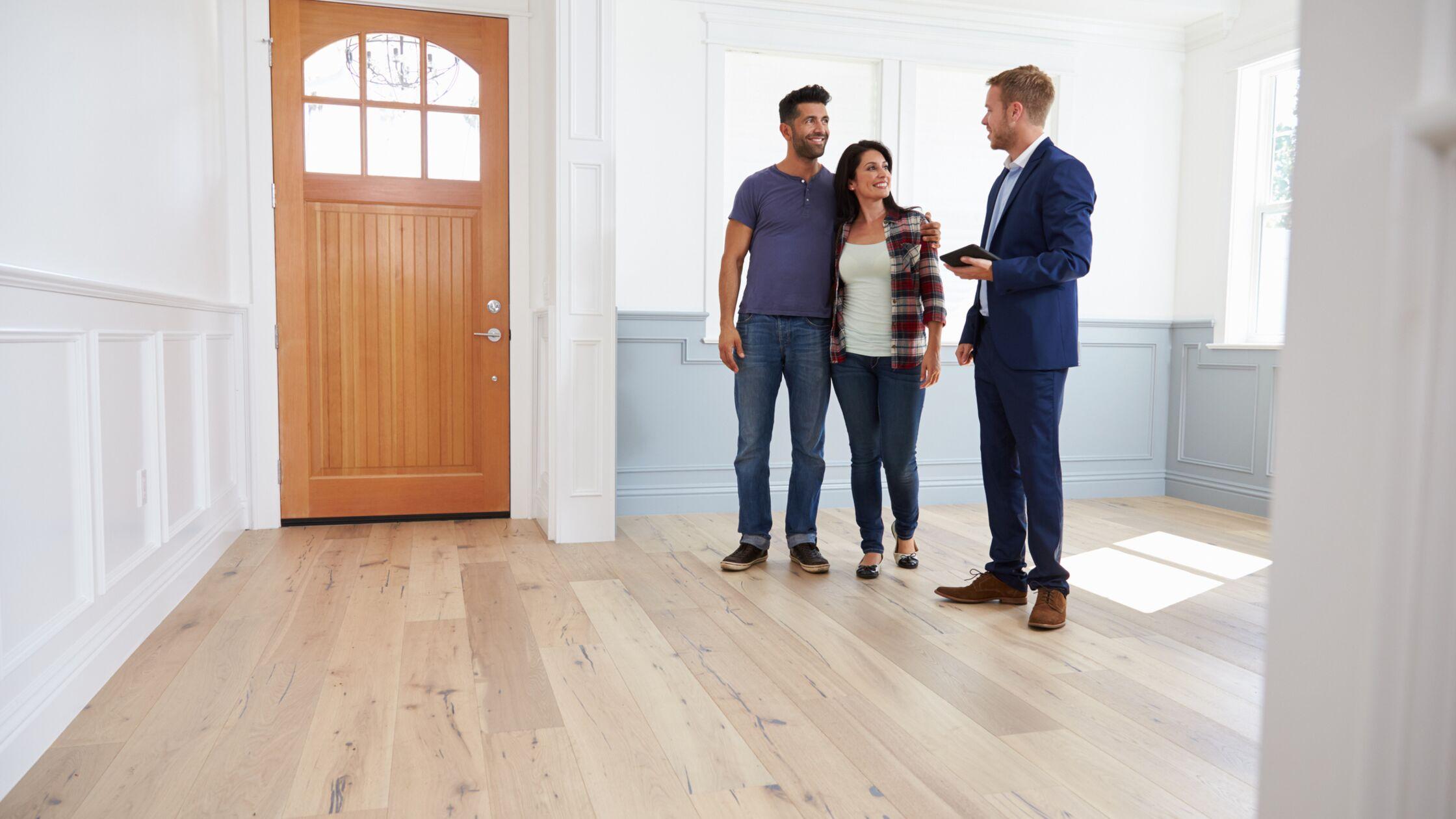 Drei Personen im Gespräch in einer leeren Wohnung