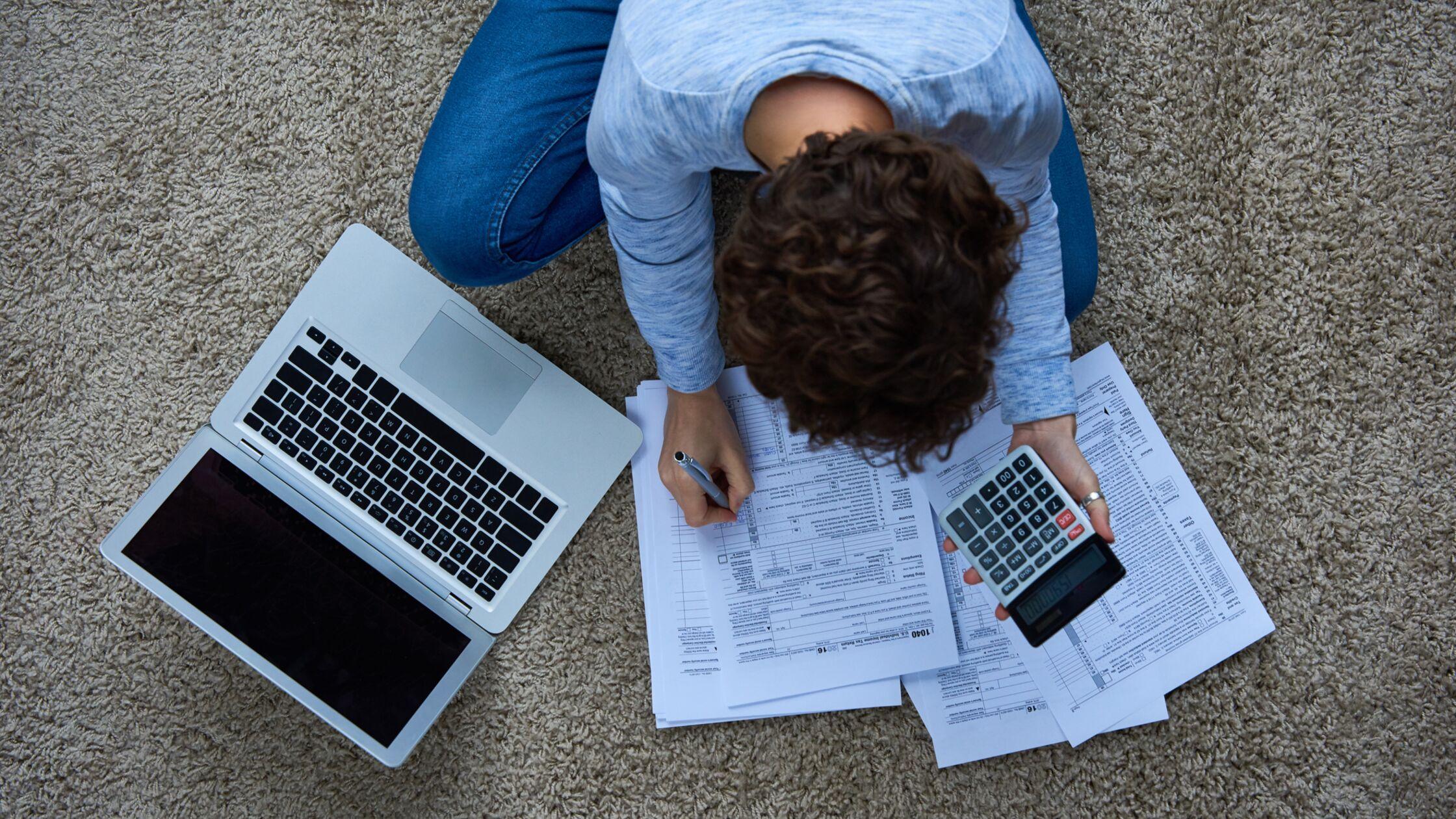 Frau sitzt auf dem Boden mit Laptop und Steuererklärung