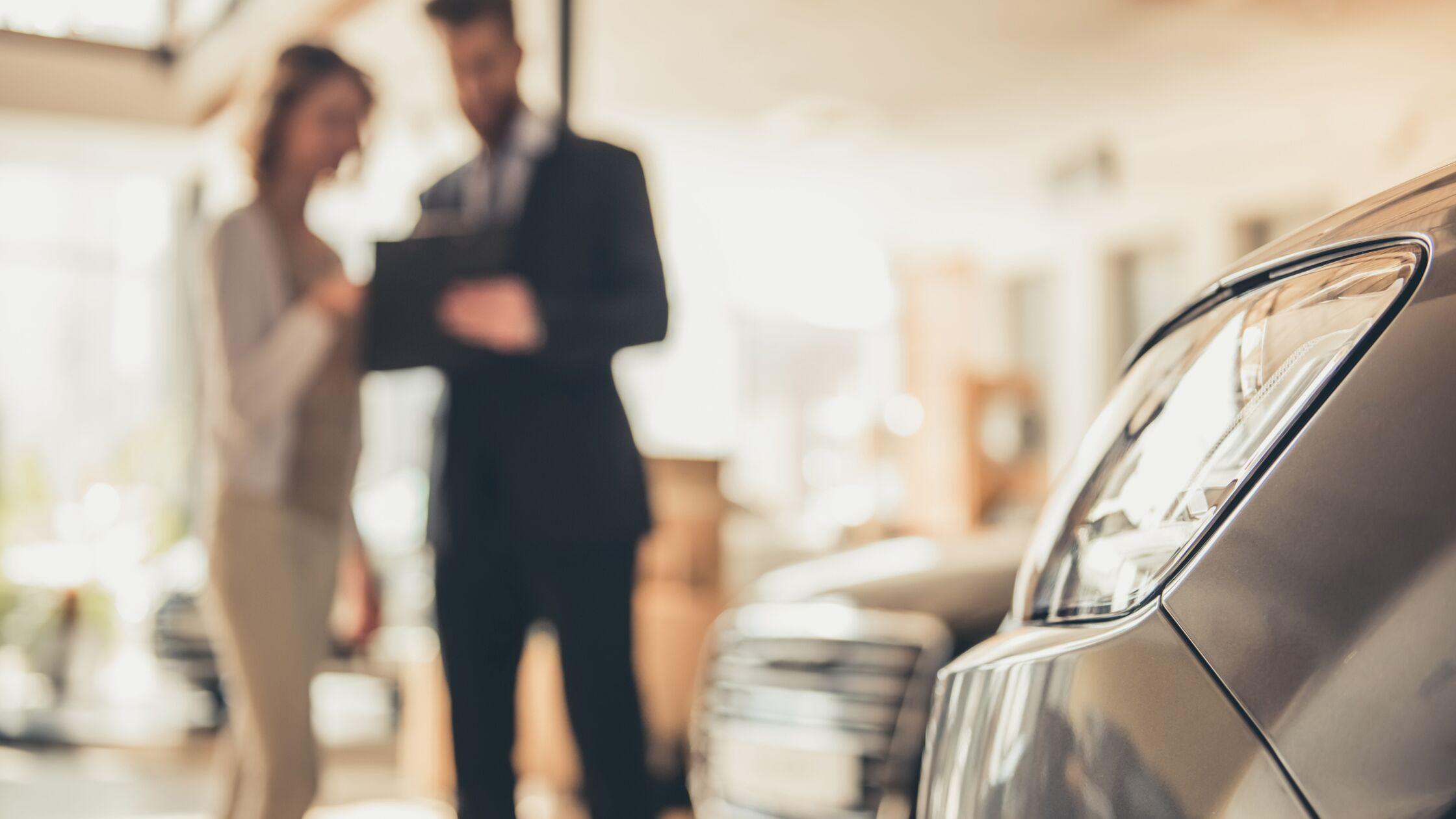 Mann und Frau führen Verkaufsgespräch im Autohaus.