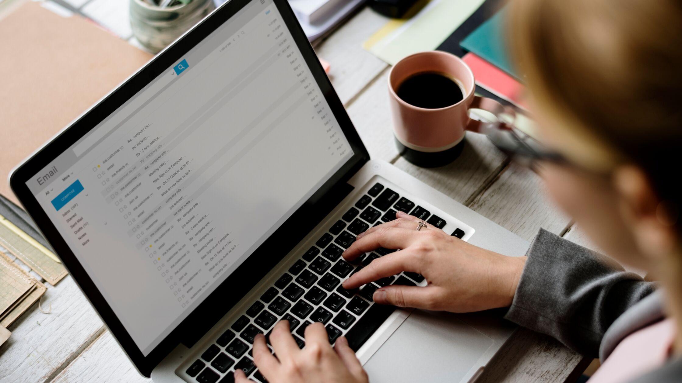 Mann schreibt auf dem Laptop eine Email an das Finanzamt, um seine Adresse zu ändern.