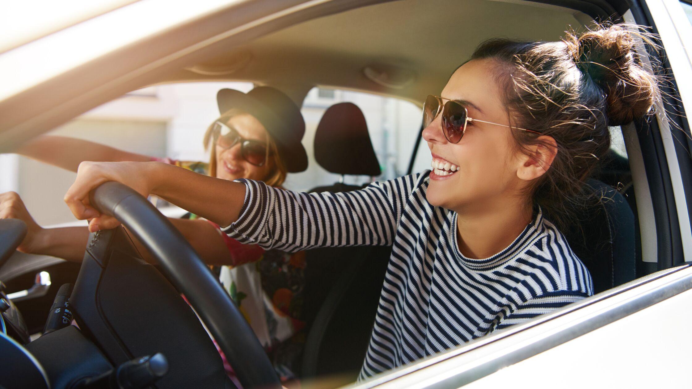 Zwei gut gelaunte Frauen fahren im Auto.