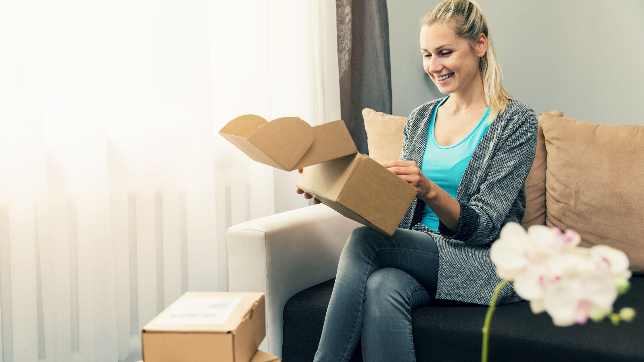 Junge Frau sitzt auf dem Sofa und öffnet Postpakete.