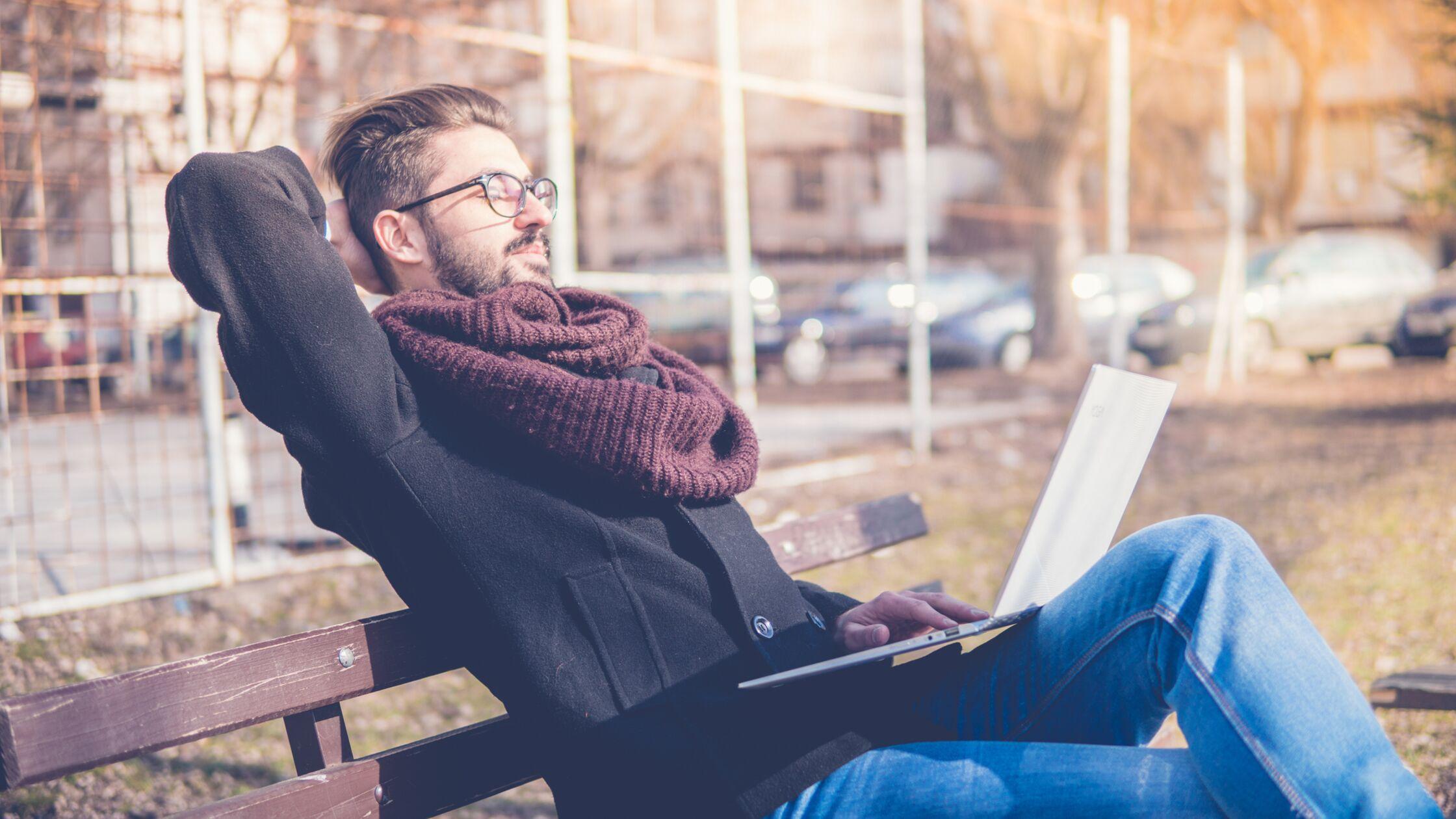 Junger Mann sitzt auf Bank und arbeitet am Laptop.