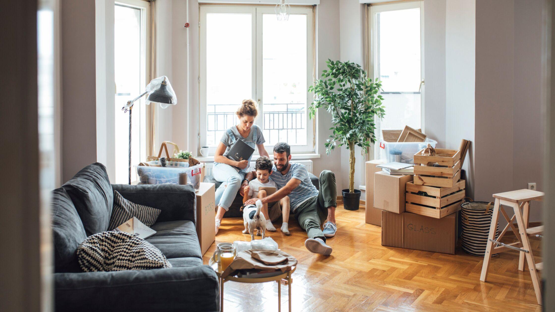 Eltern, Kind und Hund sitzen in einer neuen Wohnung neben Umzugskartons.