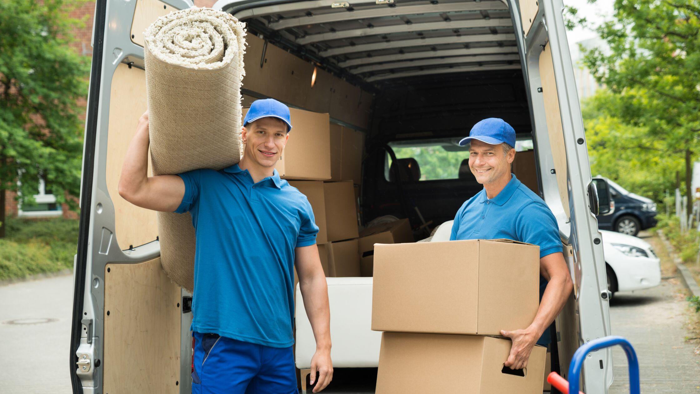 Möbelpacker mit Umzugskartons vor Umzugswagen