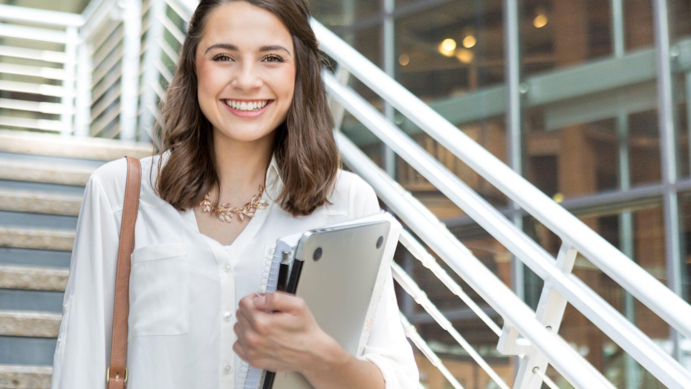 Junge Frau mit Laptop und Schreibblock in einem Treppenhaus