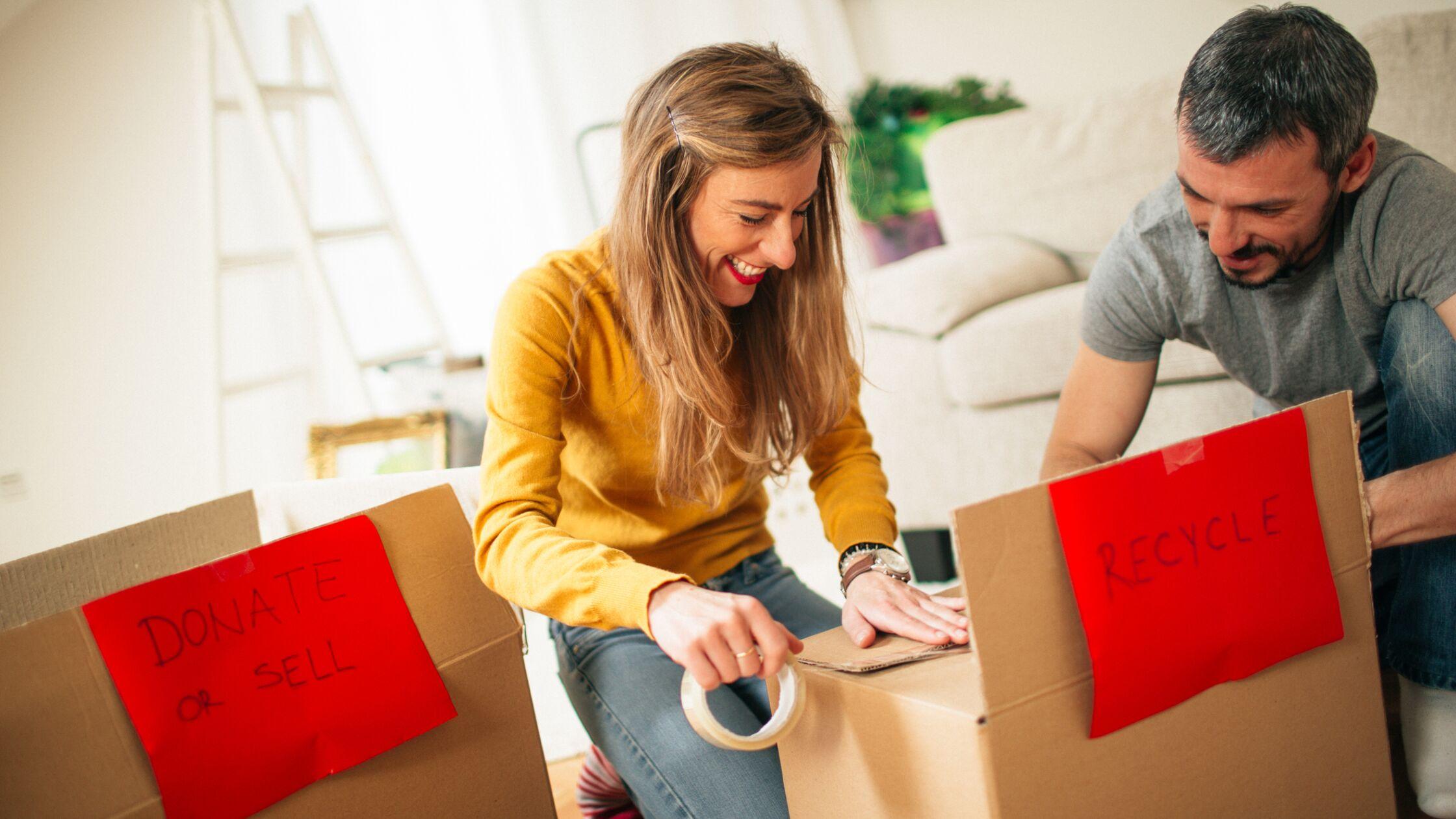 Paar packt und verschließt Umzugskartons.