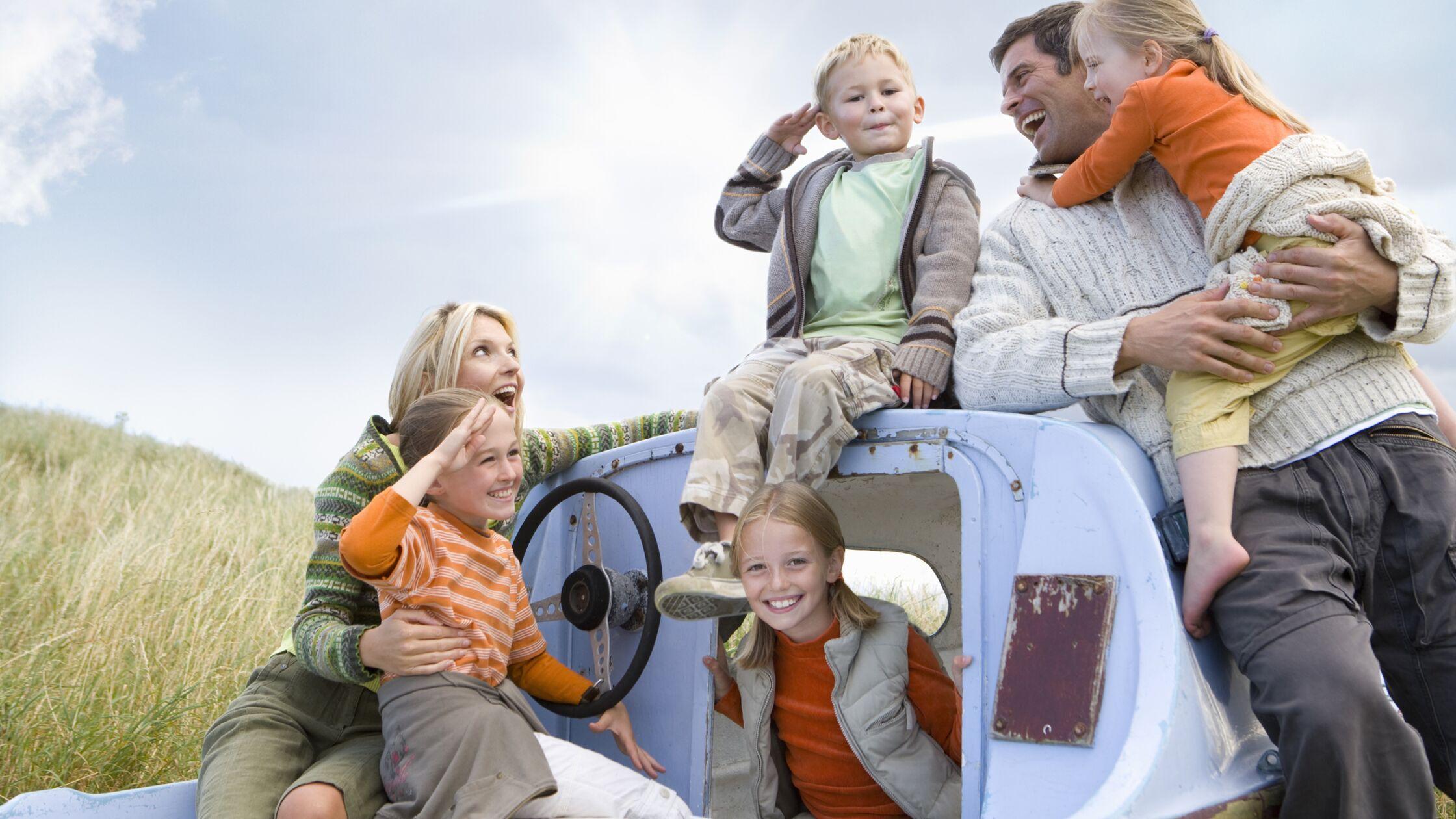 Familie mit Eltern und vier Kindern lächelnd auf Boot.
