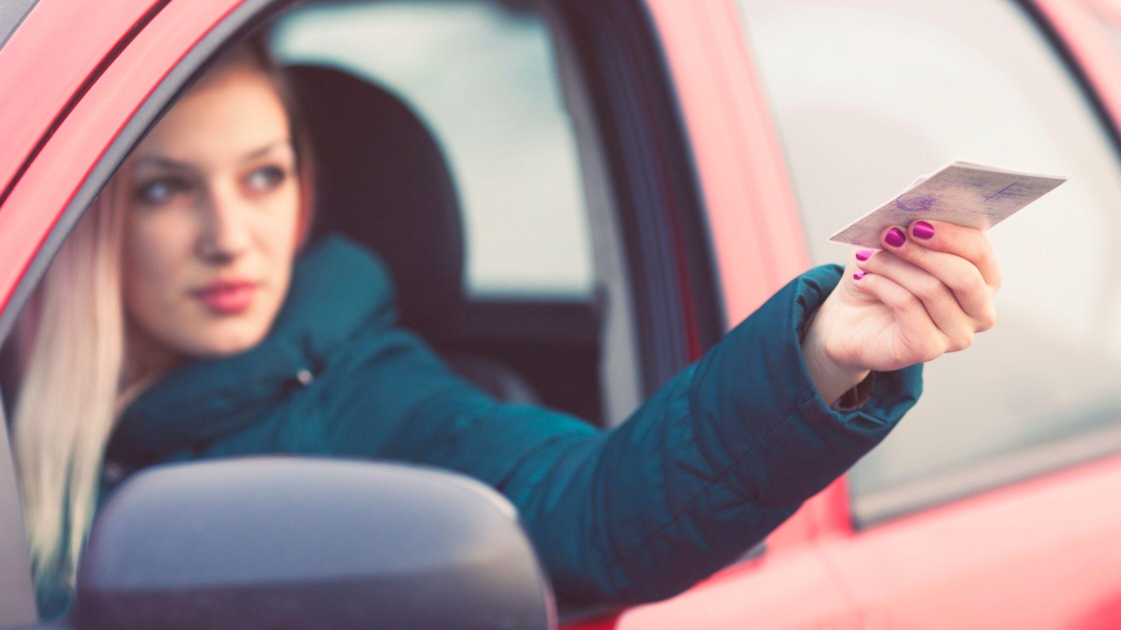 Frau sitzt im Auto und reicht Führerschein durchs Autofenster nach draußen.