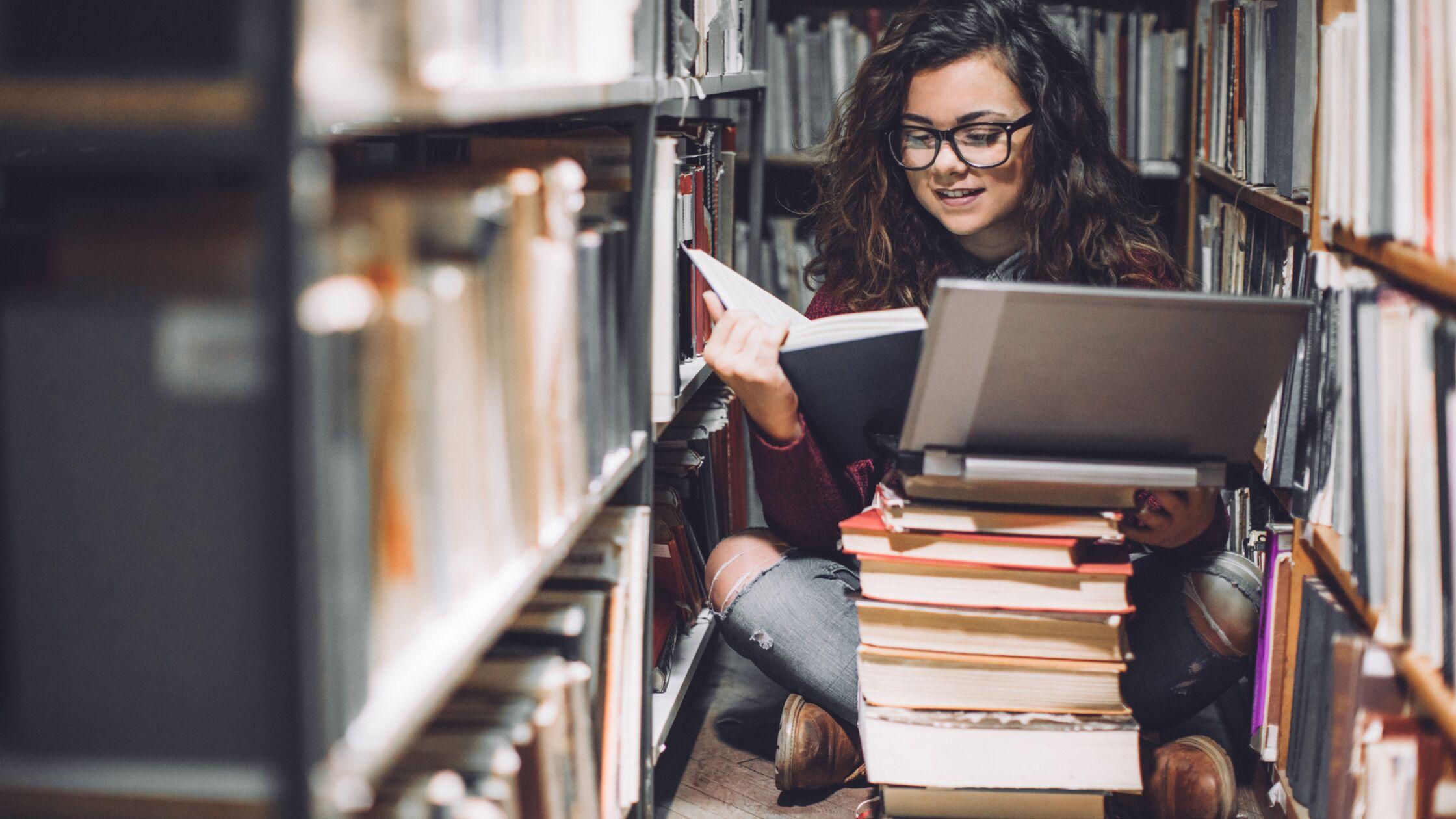 Weibliche Studentin sitzt mit Laptop auf dem Fußboden einer Bibliothek.