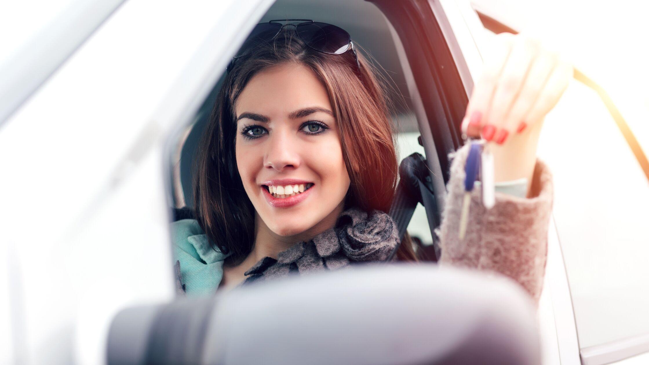 Junge Frau sitzt am Steuer und zeigt Autoschlüssel