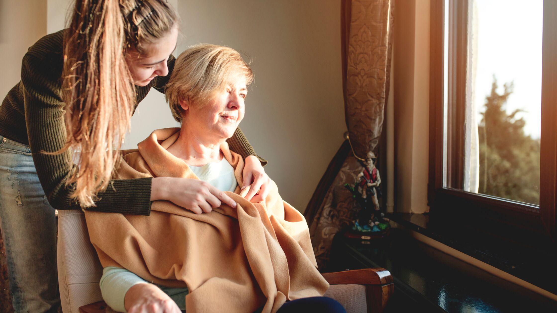 Junge Frau pflegt ältere Frau, die aus einem Fenster schaut