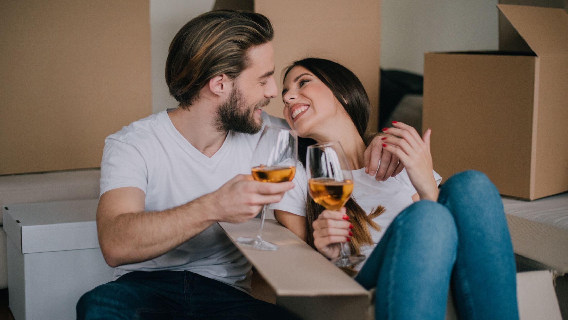 Im Hintergrund Umzugskisten, ein Paar stößt lächelnd mit Wein an.