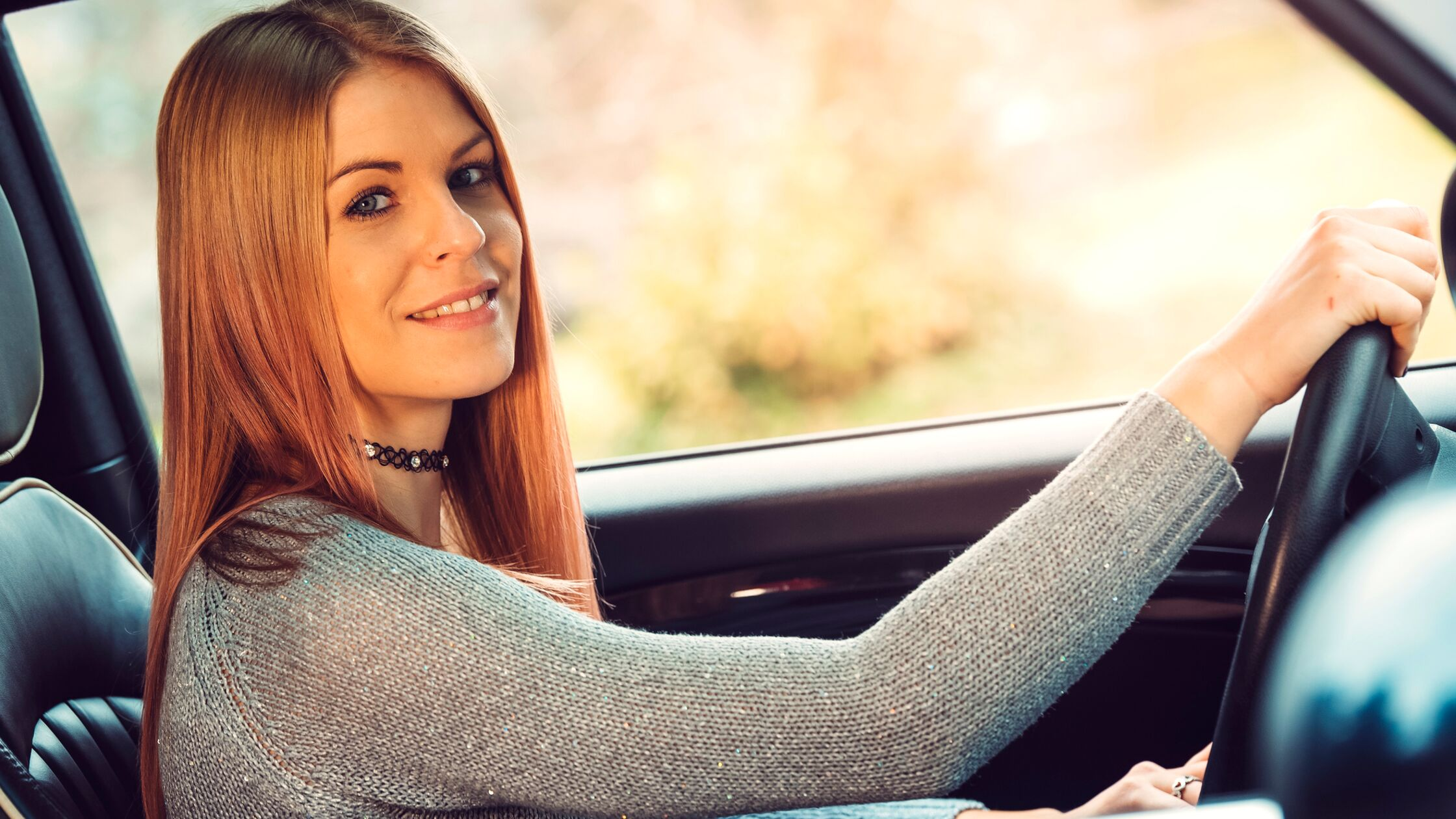 Frau sitzt hinter dem Steuer eines Autos