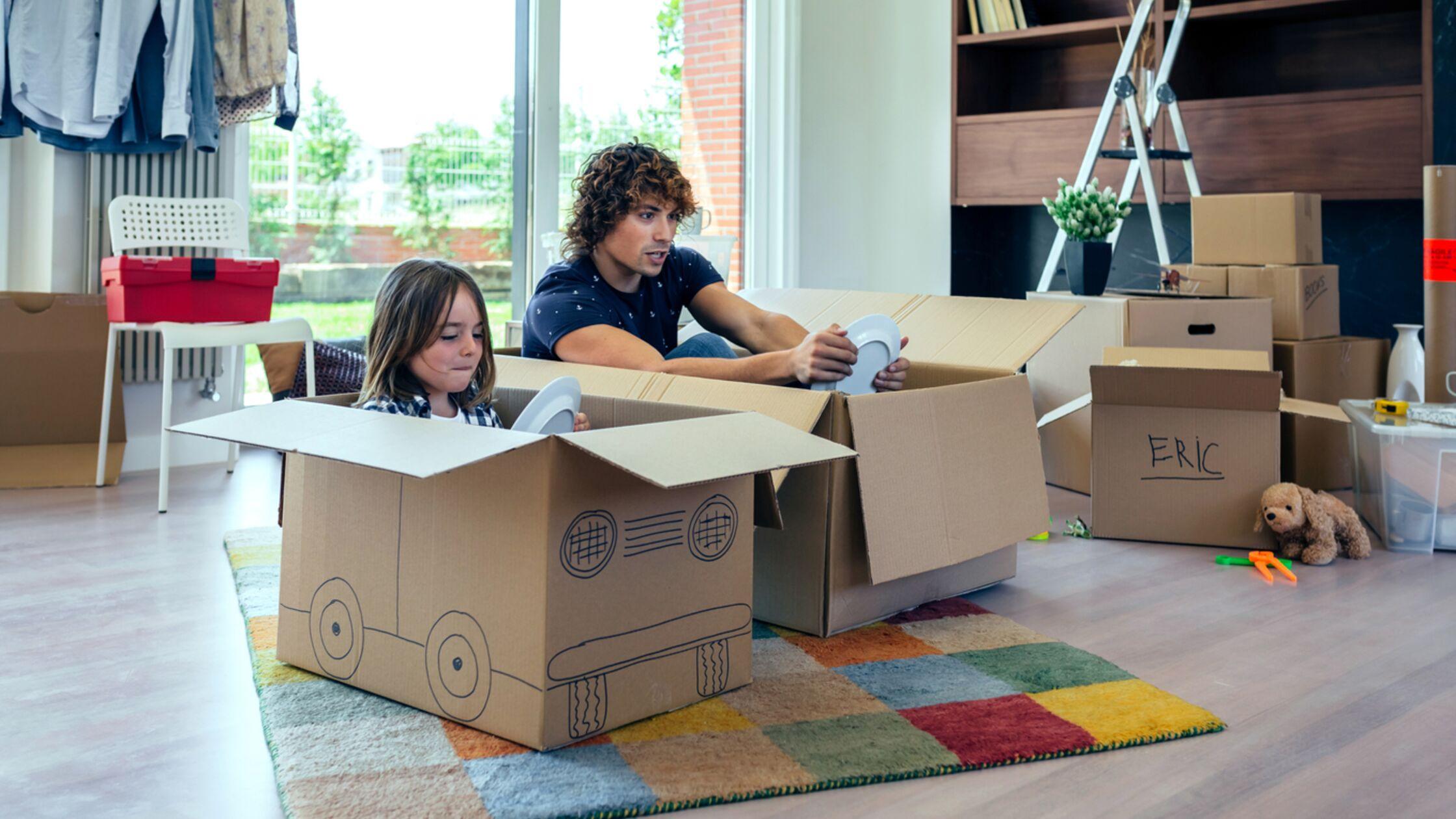 Vater und Kind sitzen in Umzugskartons und spielen Auto