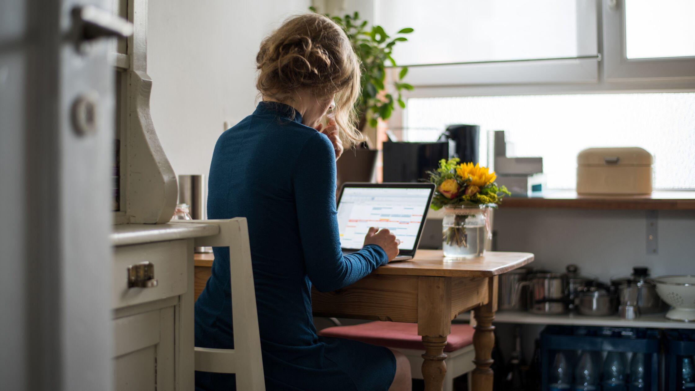 Junge Frau sitzt am Schreibtisch und arbeitet am Laptop