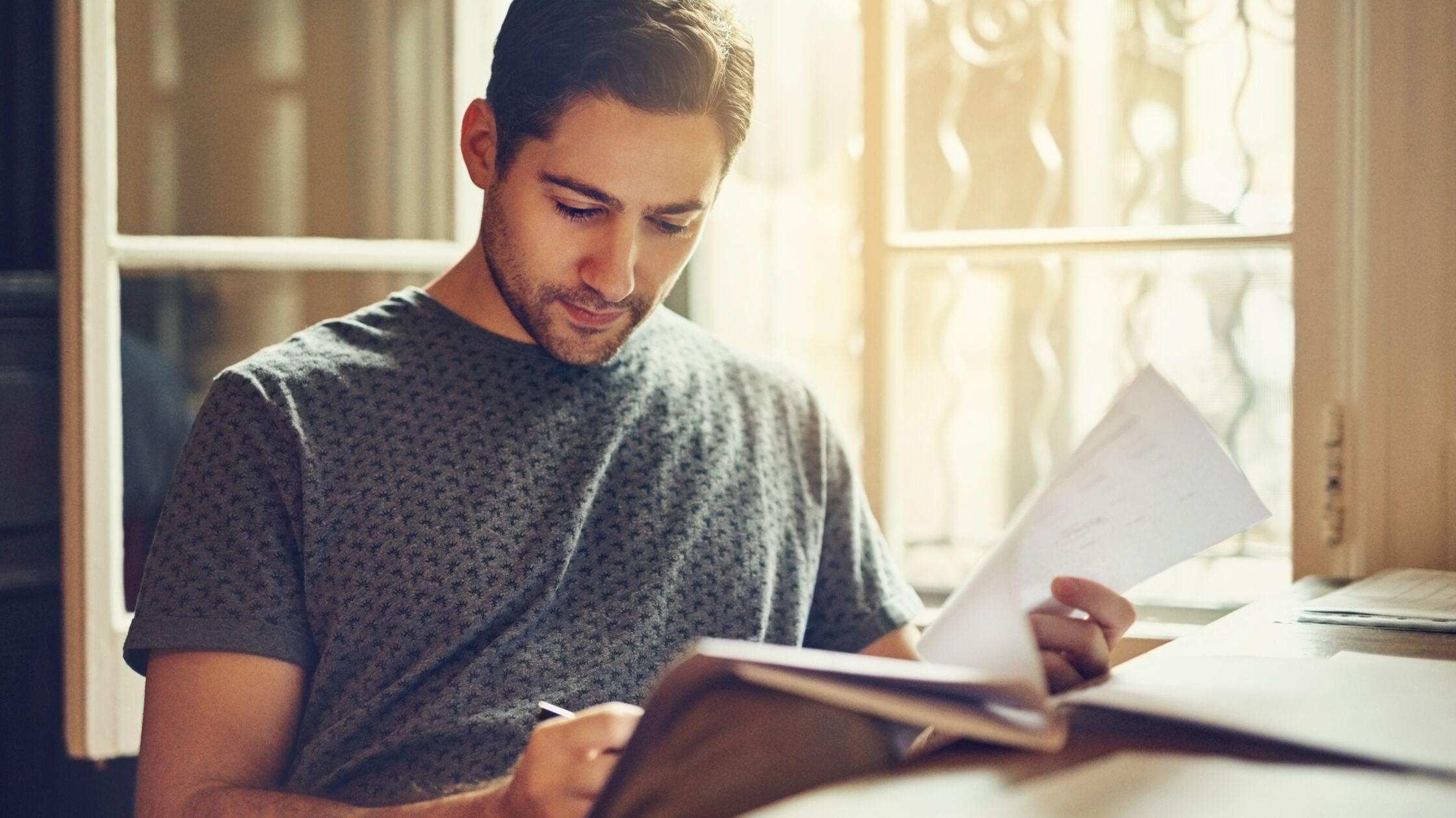 Junger Mann liest Papiere durch