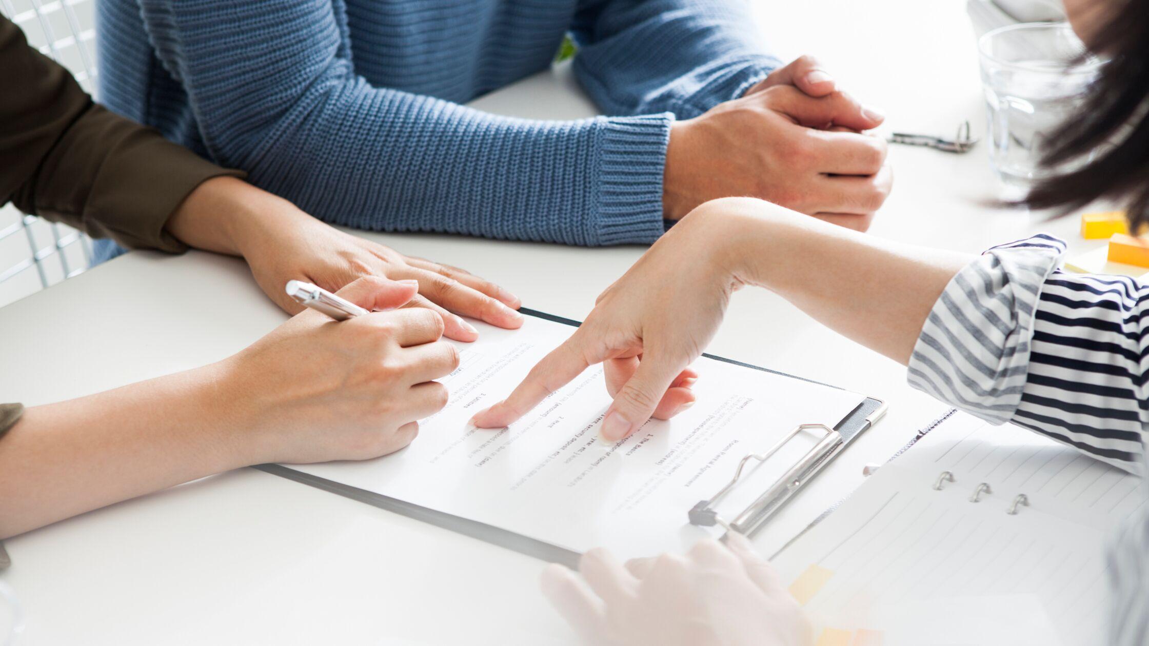 Nahaufnahme von Händen, die ein Dokument unterschreiben