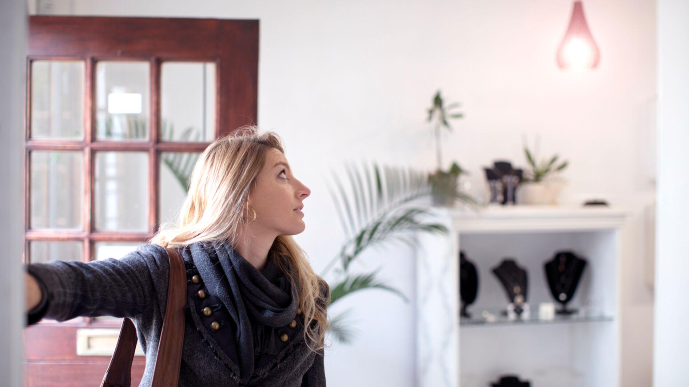 Frau schaltet Licht in neuer Wohnung ein