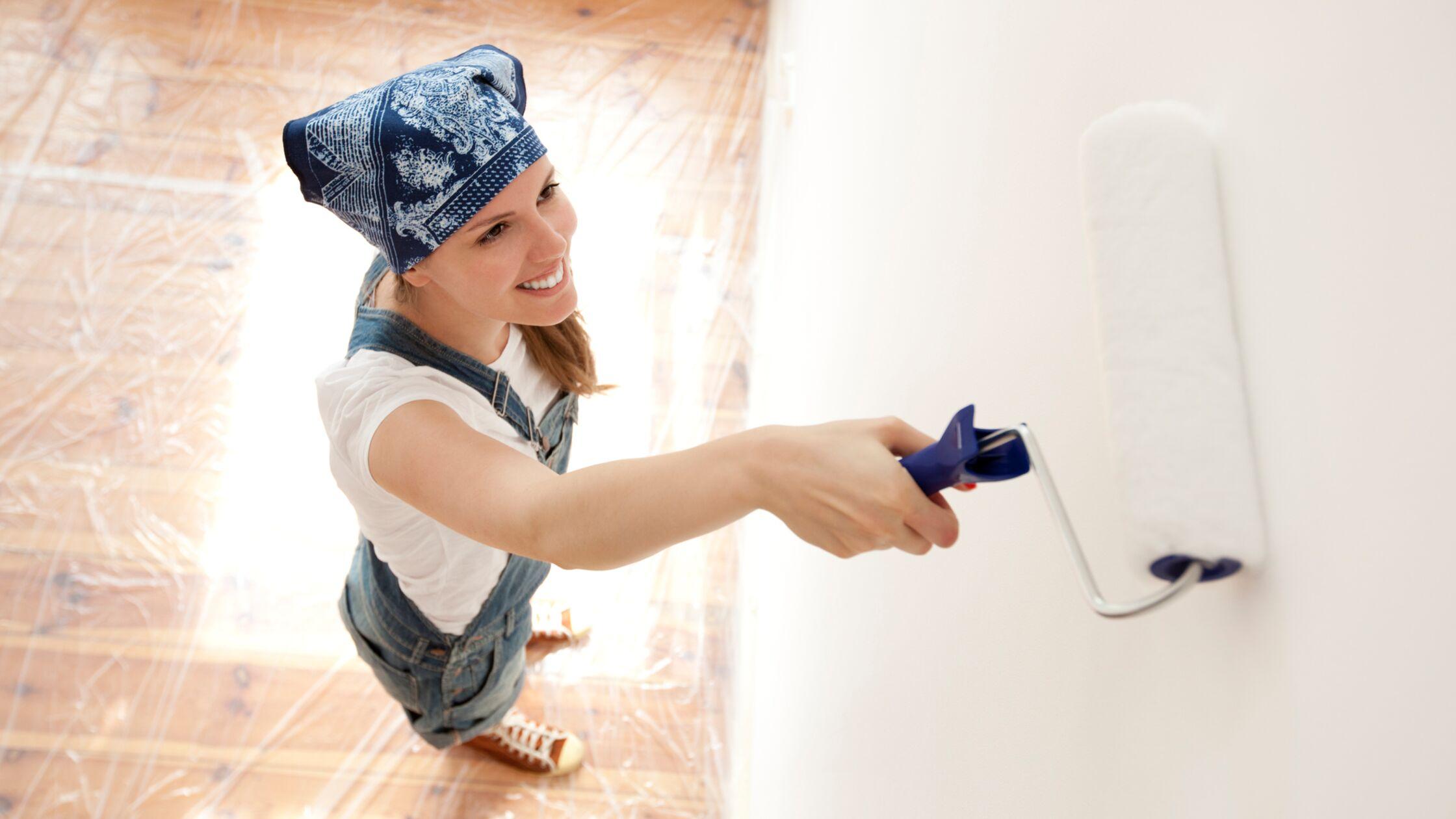 Junge Frau streicht eine Wand.