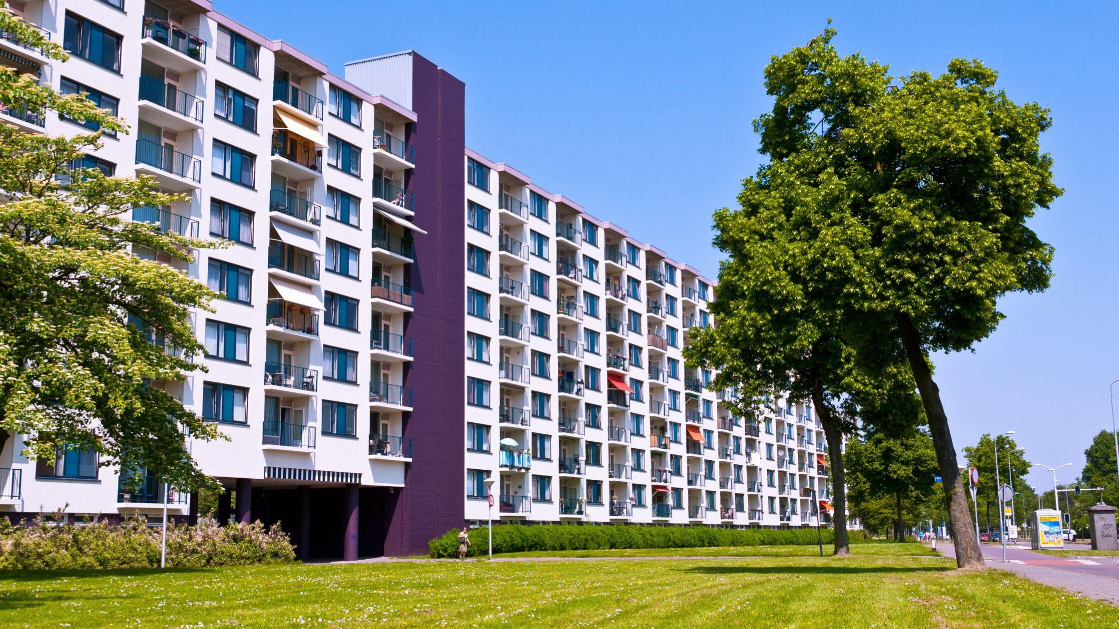 Wohnblock mit vielen Wohnungen von außen, davor Rasen und Bäume