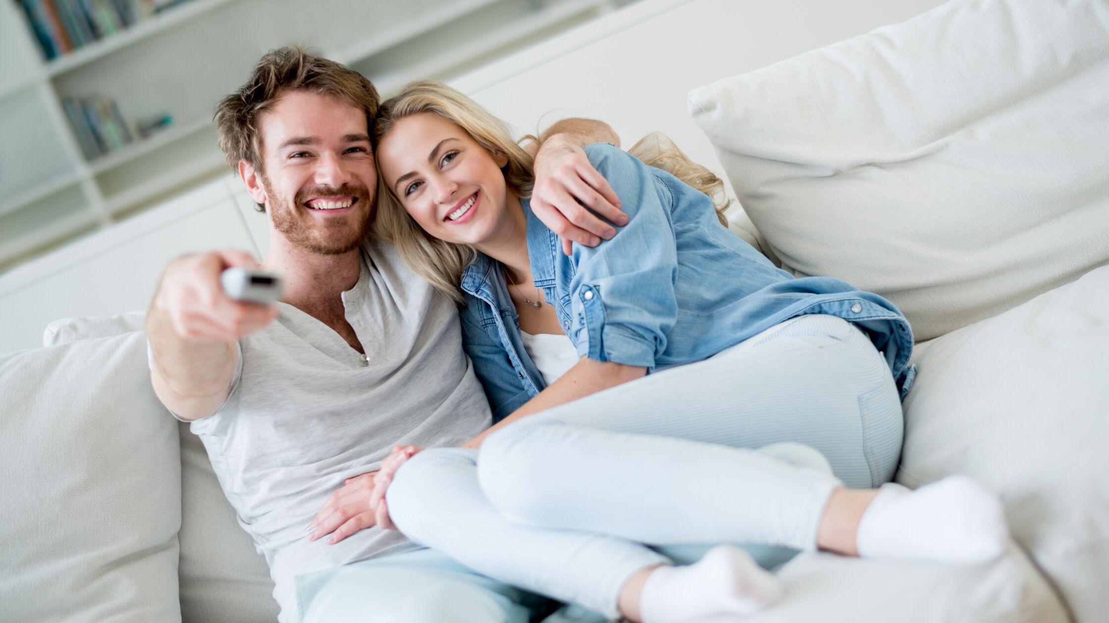 Paar auf Couch mit Fernbedienung