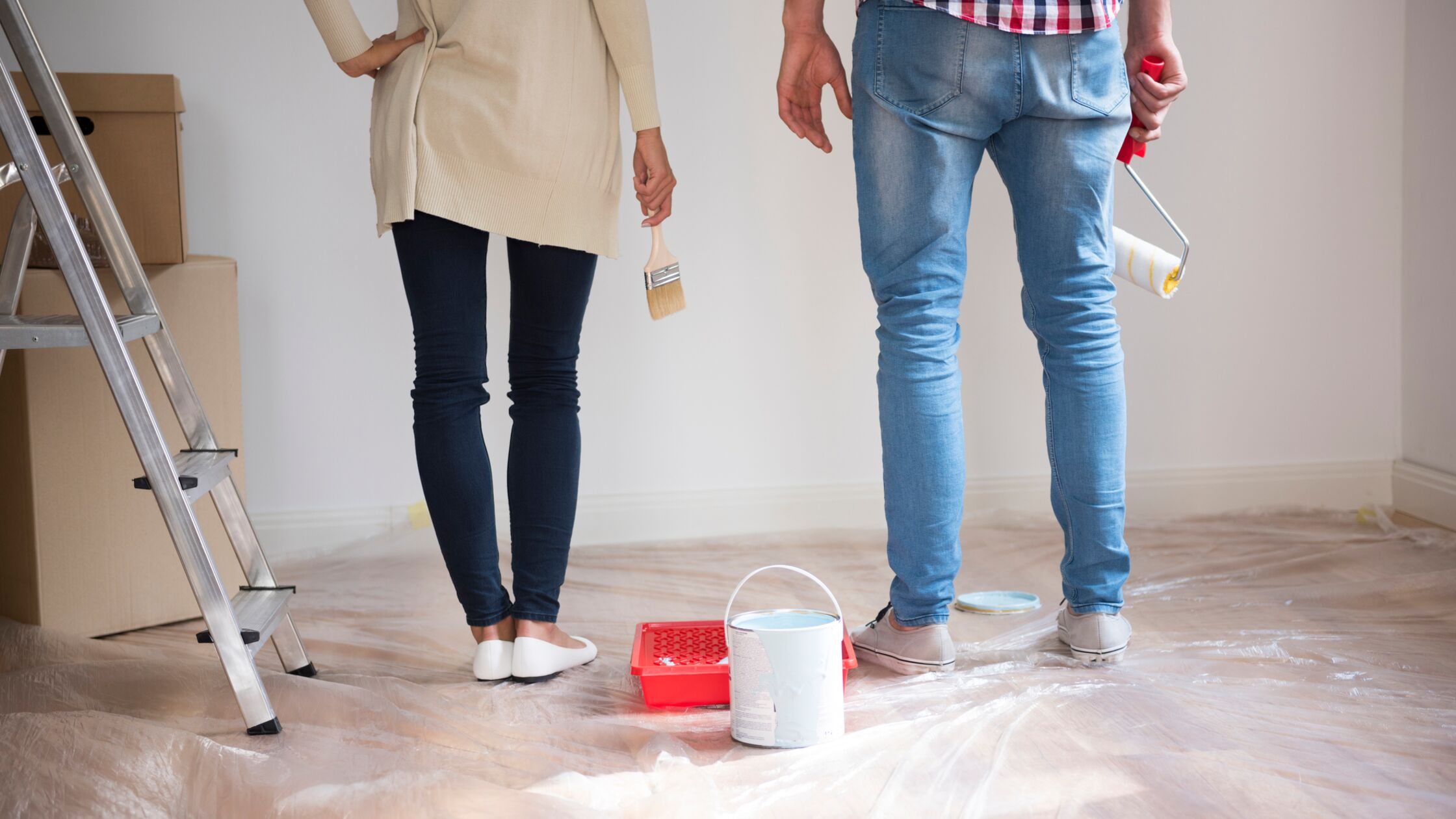 Mann und Frau mit Malerutensilien stehen vor einer Wand