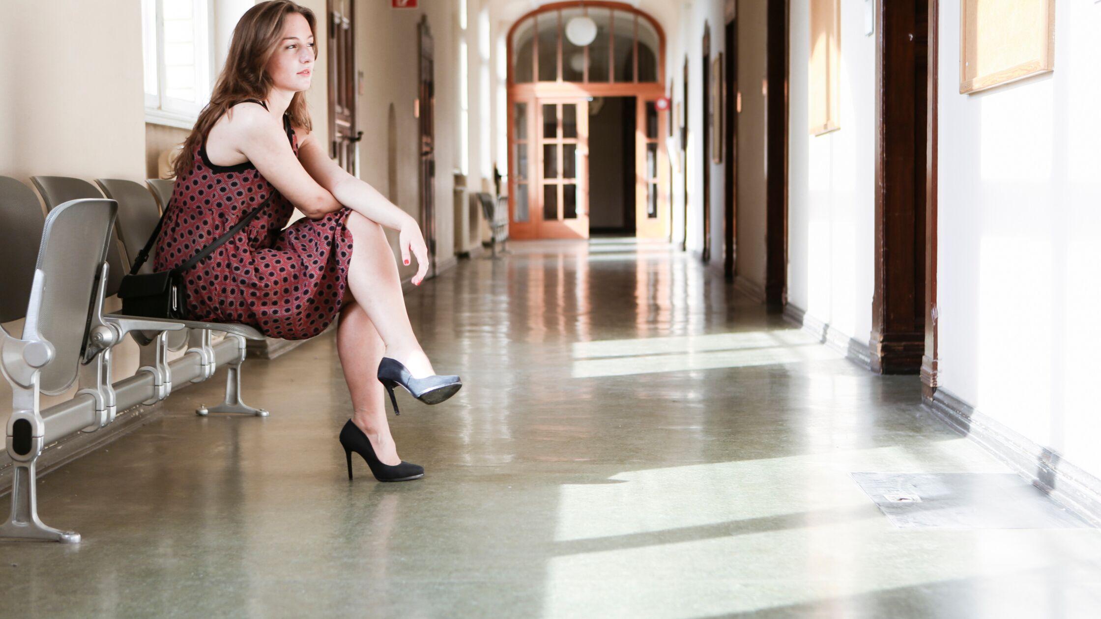 Frau sitzt auf dem Flur und wartet