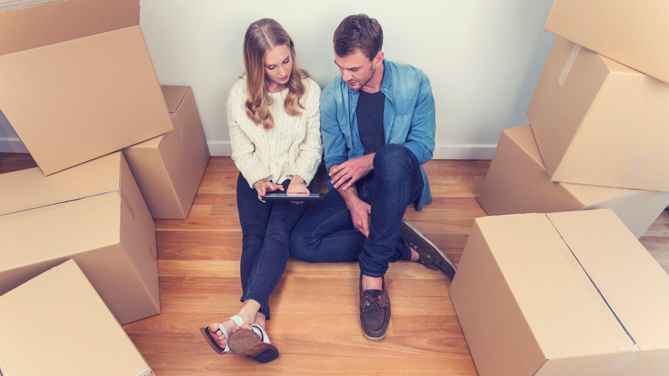 Paar sitzt zwischen Umzugskartons und schaut gemeinsam auf ein Tablet