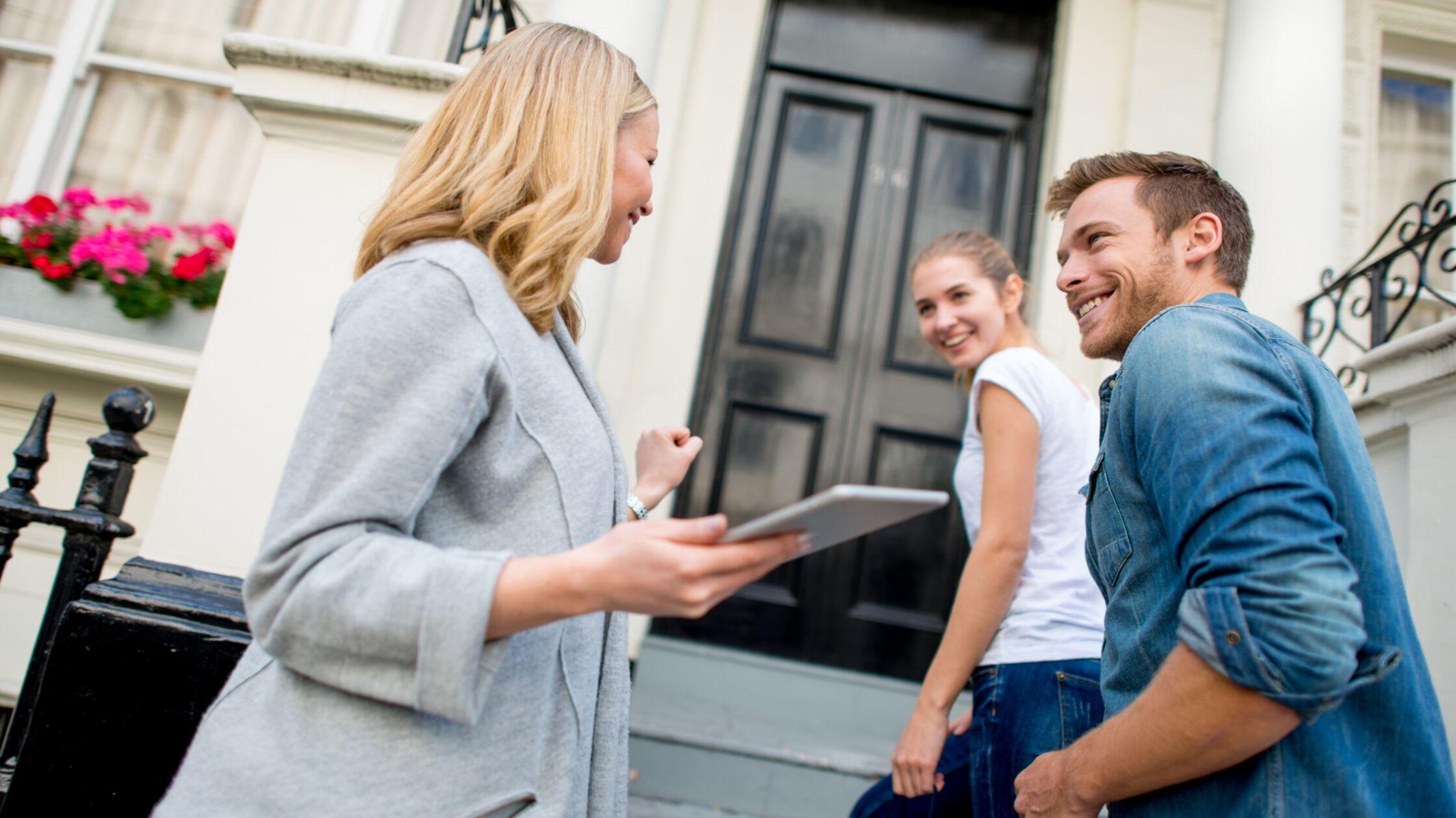 Paar betritt mit Maklerin oder Vermieterin neues Haus über Außentreppe
