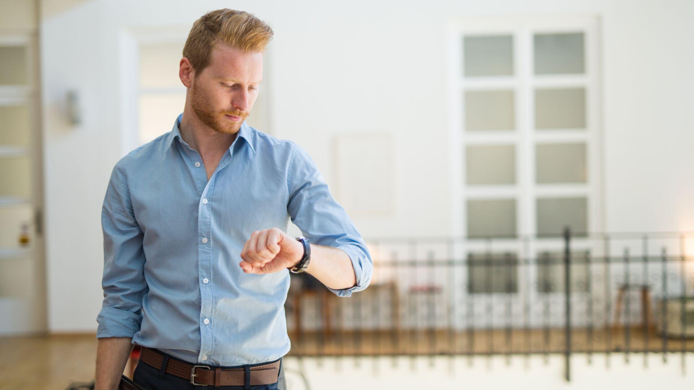 Junger Mann schaut auf seine Armbanduhr