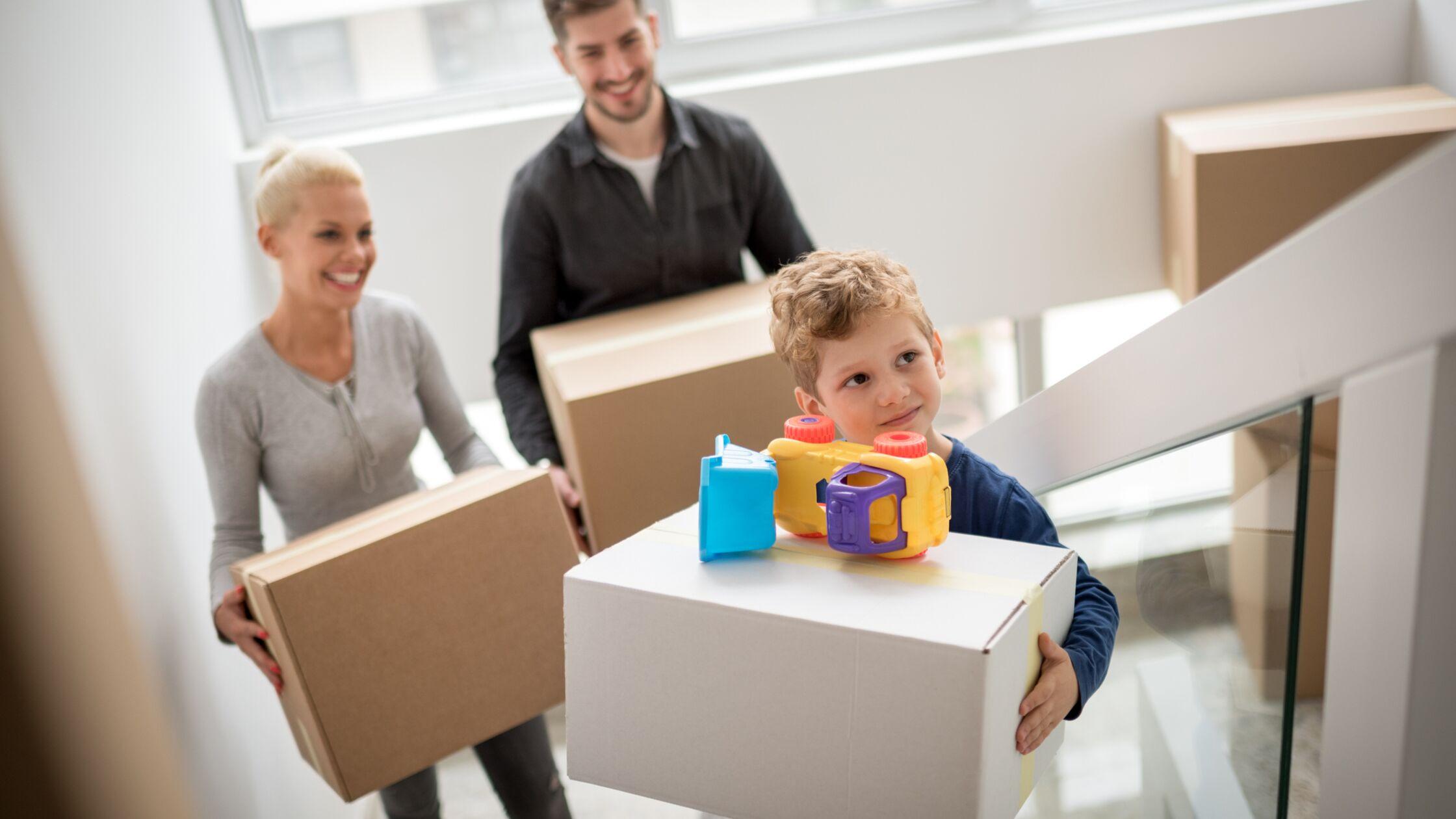 Mann, Frau und Kind gehen mit Umzugskartons eine Treppe hoch