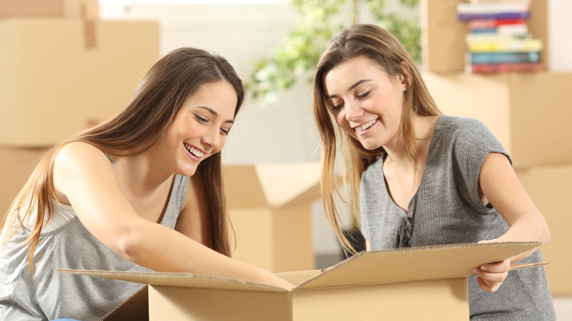 Zwei junge Frauen über geöffnetem Umzugskarton, im Hintergrund weitere Kartons.